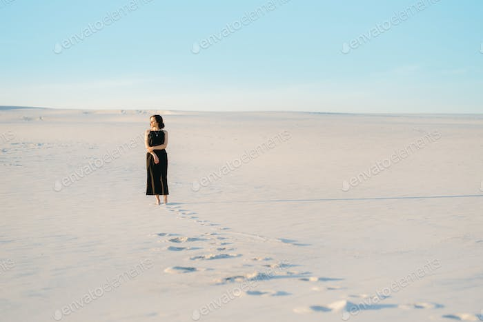 girl in a black dress stands in the middle of the desert