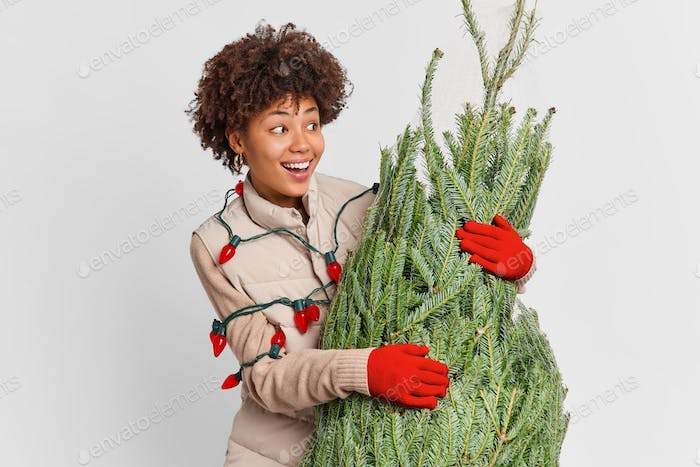 Isolated shot of positive Afro American woman looks aside happily notices beautiful christmas toys i