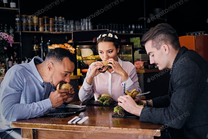 Three people eats sandwiches.