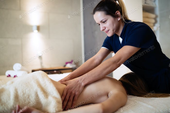 Masseur massaging back of female