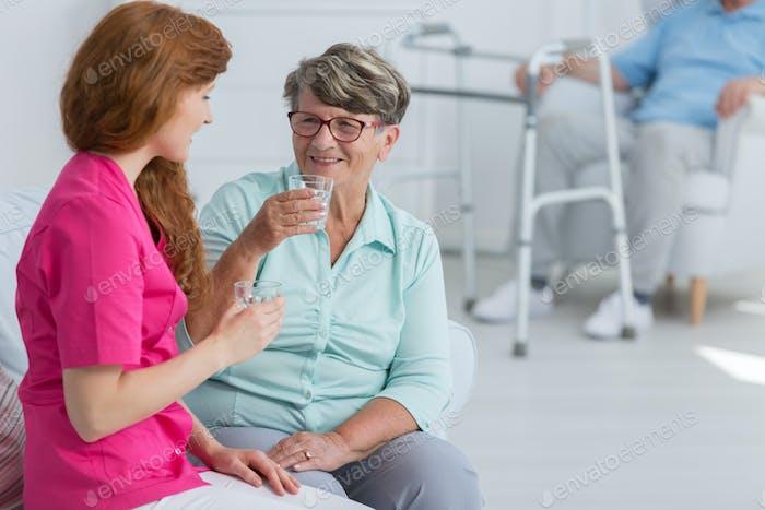 Krankenschwester Trinkwasser mit Senior Frau