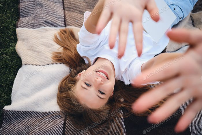 Beautiful smiling teenage girl lying on plaid happily pulling hands up to camera on picnic in park
