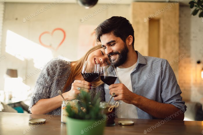 Cheers! Happy couple is drinking wine at cafe during a day