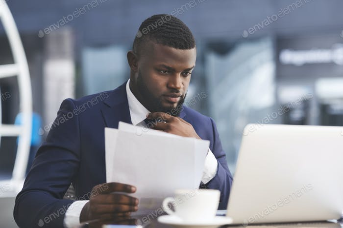 Serious Businessman Working On Laptop Holding Papers In Outdoor Cafe