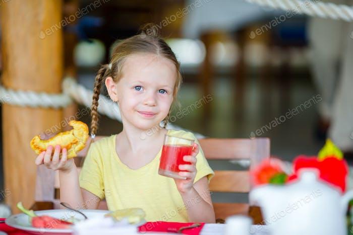 Entzückend kleines Mädchen mit Frühstück im Freien Café