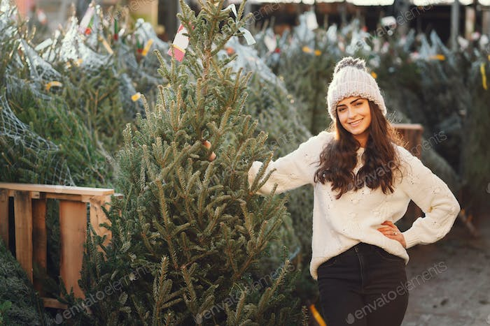 Cute brunette in a white sweater with Christmas tree