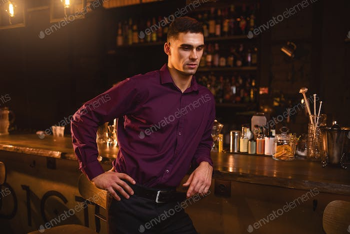 Young man in shirt standing at the bar counter