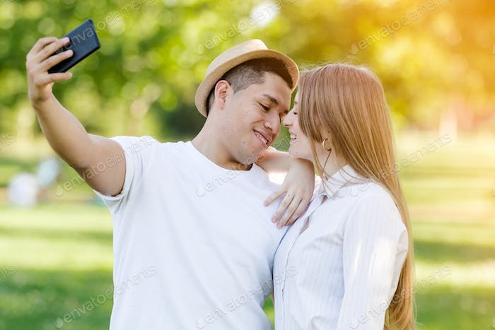 Young couple taking a selfie on their mobile in the park. Latin man and Caucasian woman