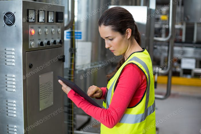 Female factory worker using digital tablet