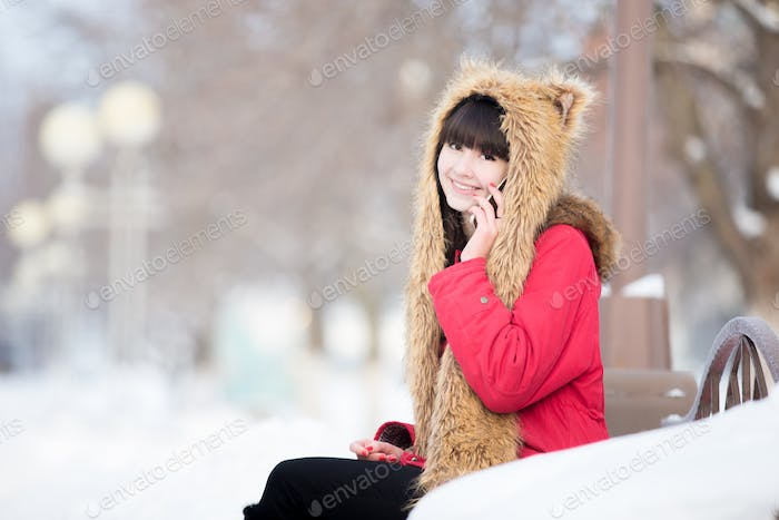 Young woman on phone on the bench outdoors in wintertime