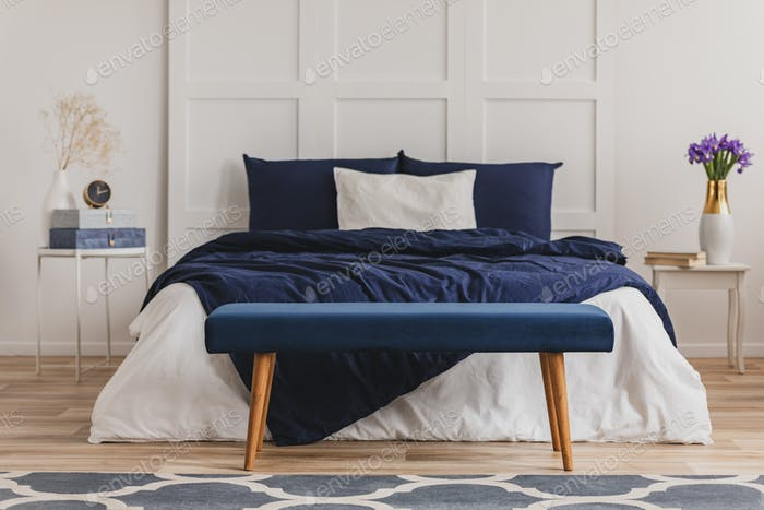 Velvet petrol blue bench in front of comfortable big bed with cozy bedding