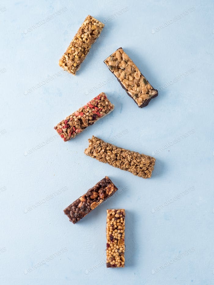 Set of different granola bars on blue background