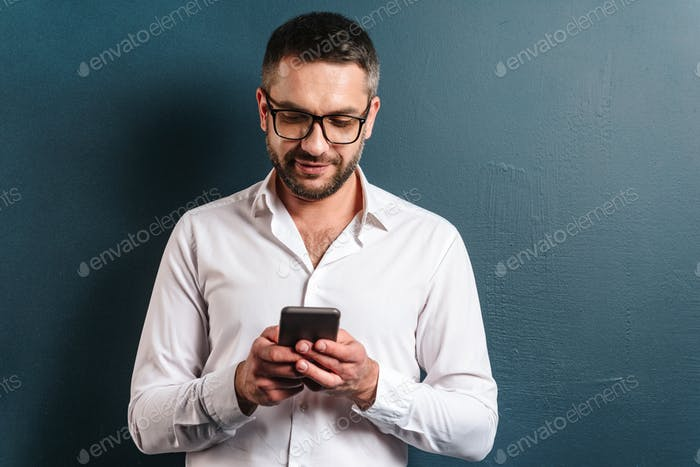 Cheerful man wearing glasses chatting by phone.