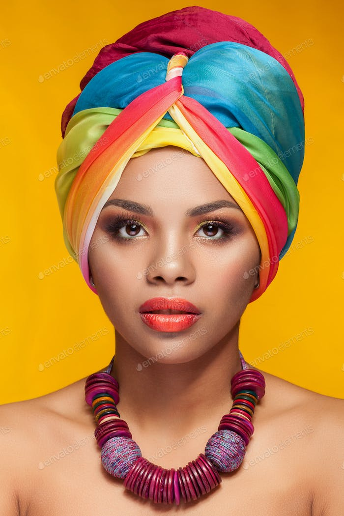 Young woman with afro american turban on yellow background