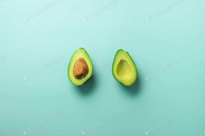 Green avocado halves with seed on blue pastel background. Creative minimal flat lay style with copy