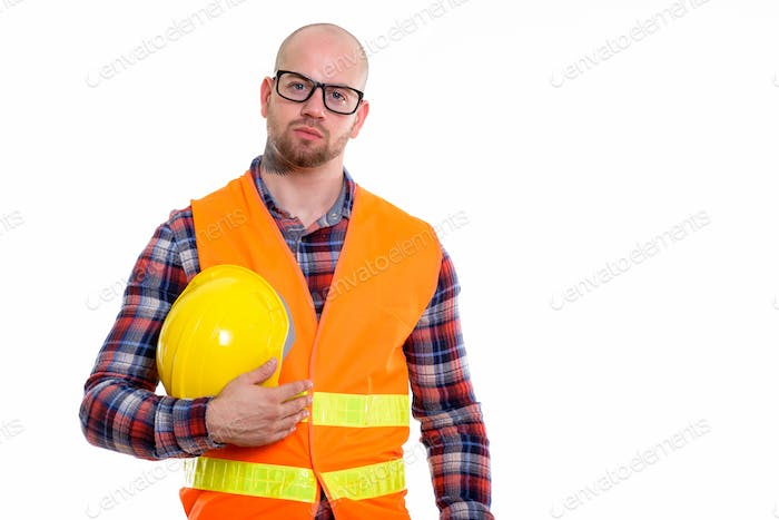 Young bald muscular man construction worker isolated against white background