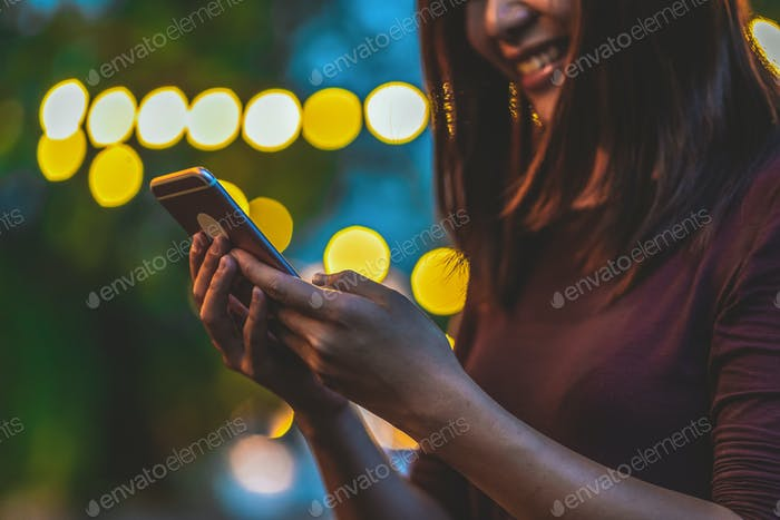 Closeup hand of Asian woman using smartphone and touching screen at outdoor park,