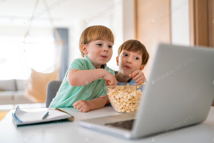 Cute children playing, watching movie on laptop at home. Digital addiction concept