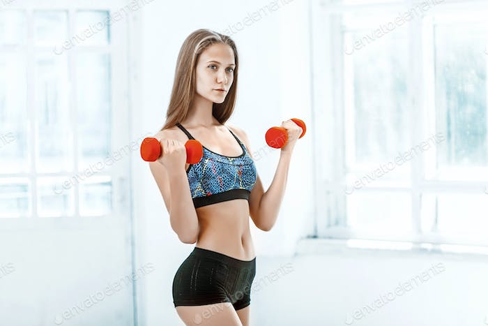 Sporty woman doing aerobic exercise with red dumbbells