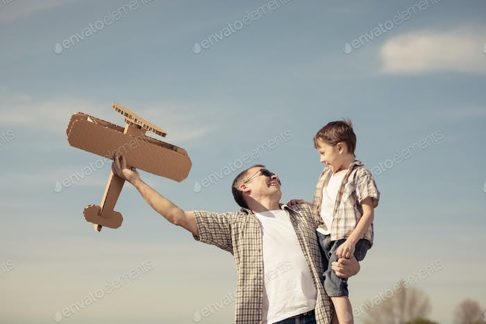 Father and son playing with cardboard toy airplane in the park a