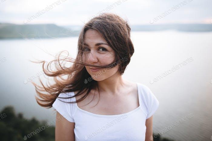 Calm portrait of brunette woman in white shirt