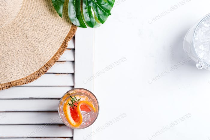 Cold summer drink in a glass with slice of grapefruit and ice cubes and Wide-brimmed hat and green
