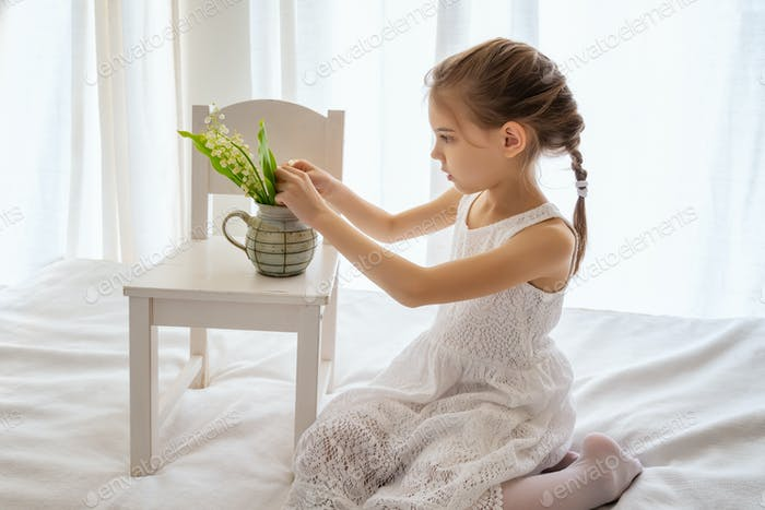 Little girl and lily of the valley