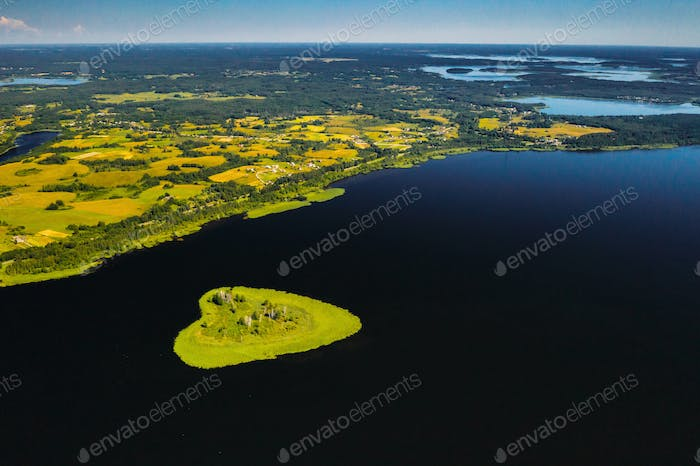 Love island on a lake in Europe, a Green heart-shaped Island on a dark lake with a sparkle from the