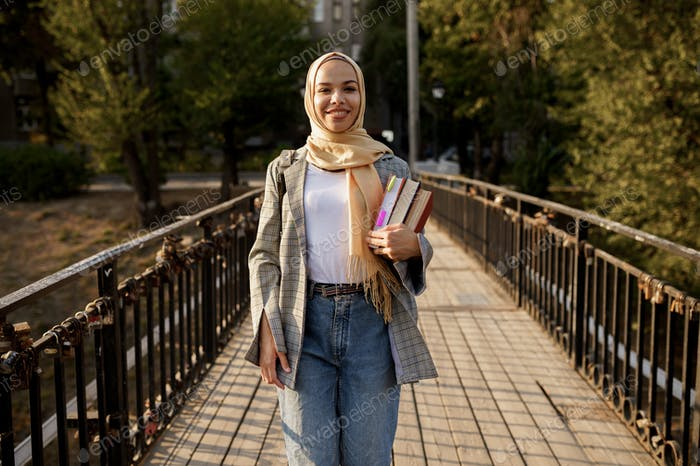 Arab girl in hijab holds textbooks in summer park