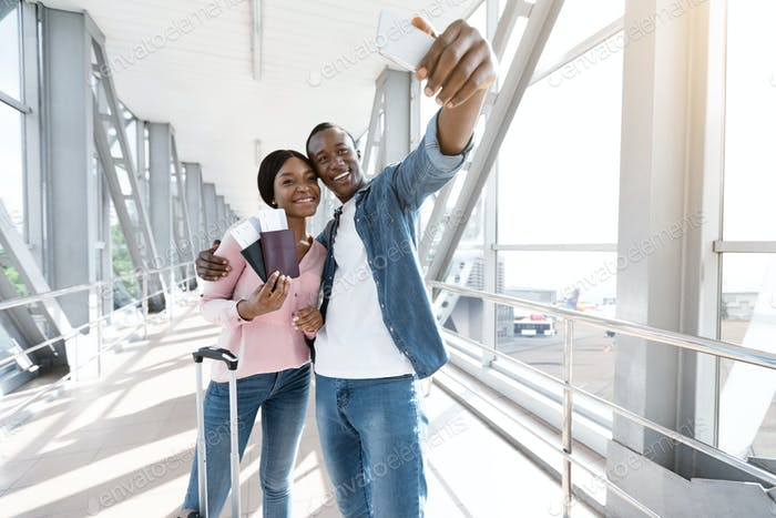 Vacation Selfie. Happy African American Couple Taking Photo On Smartphone In Airport