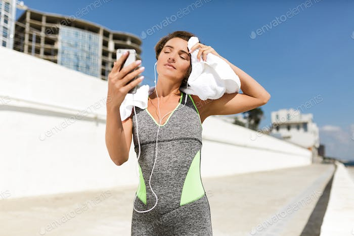Beautiful woman in modern sport suit holding towel on shoulder dreamily looking on cellphone