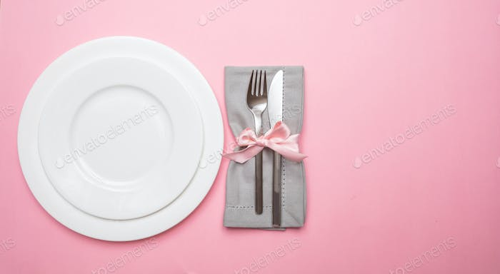 Table place setting in pink. Gray linen napkin with ribbon and white plates on pink color background