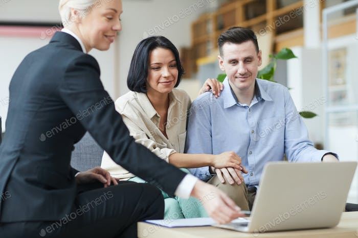 Realtor and couple using laptop