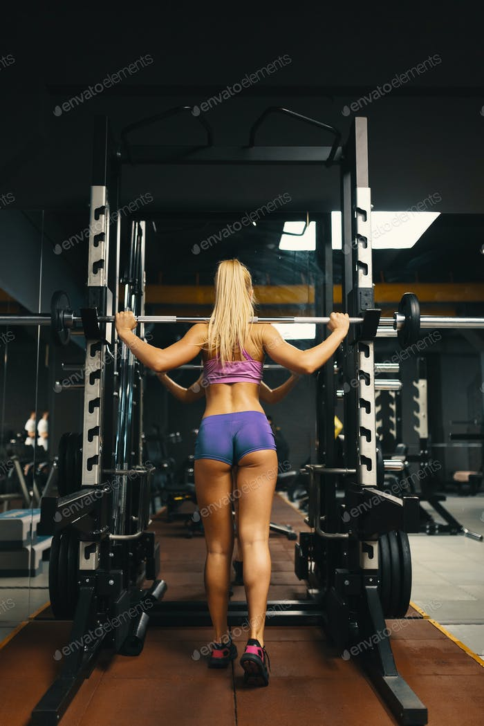 Back view, sporty girl in pink top and mini shorts, raising the bar preparing for squats