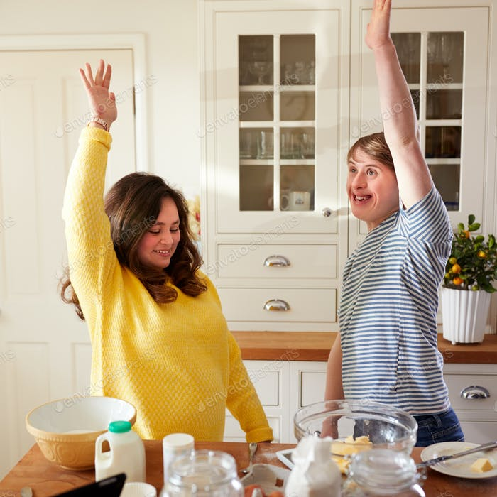 Young Downs Syndrome Couple Having Fun Baking In Kitchen At Home