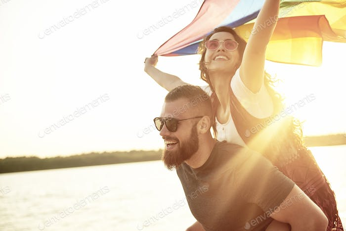Young woman waving rainbow flag on men's arms
