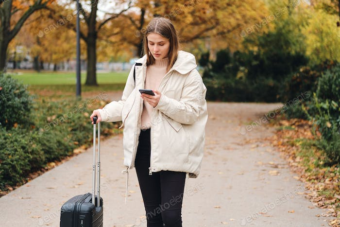 Attractive girl in down jacket with suitcase thoughtfully looking way on cellphone outdoor