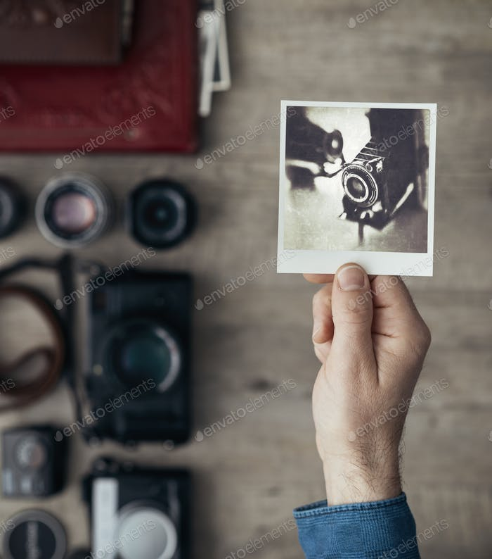 Photographer holding an instant picture
