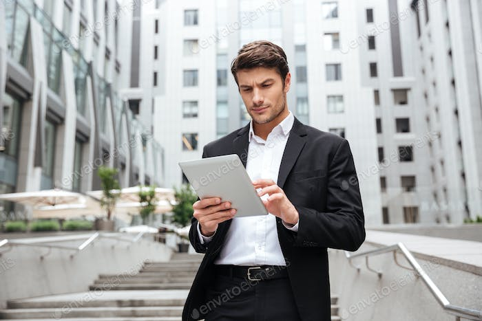 Serious businessman walking and using tablet in the city