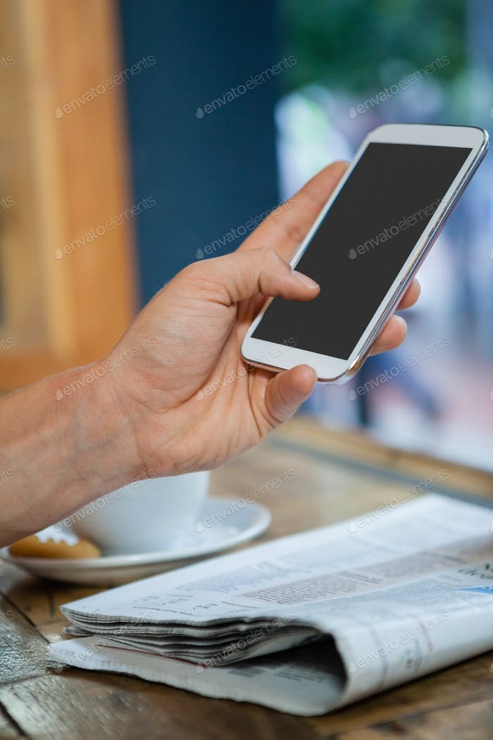 Cropped image of woman holding mobile phone at table