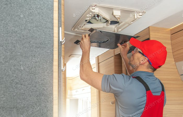 Men Repairing Air Condition Unit Inside Modern Travel Trailer
