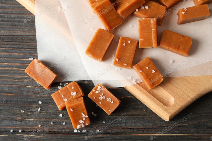 Salted caramel candies on wooden background, close up