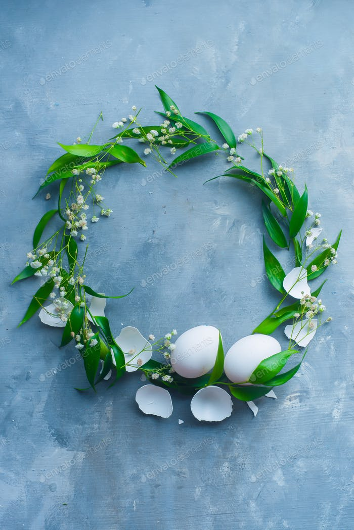 Easter wreath with eggs, green leaves and spring flowers. Floral decoration concept with copy space.