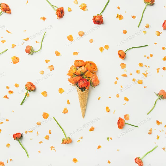 Waffle cone with orange buttercup flowers. Spring or summer mood concept