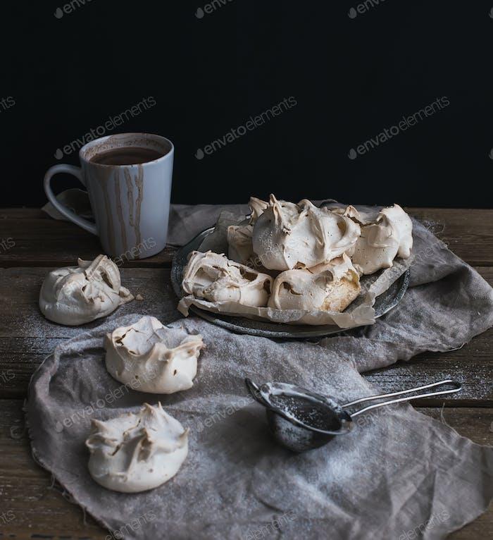 Baiser und Tasse heiße Schokolade auf einem rustikalen Holztisch. Schwarzer Hintergrund