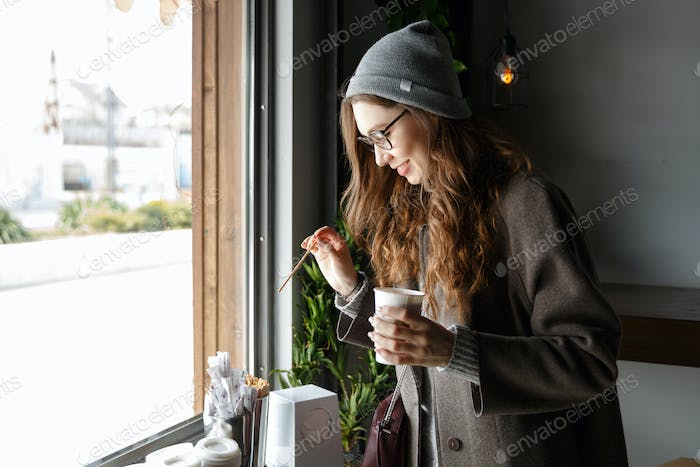 Happy attractive young woman drinking coffee in cafe