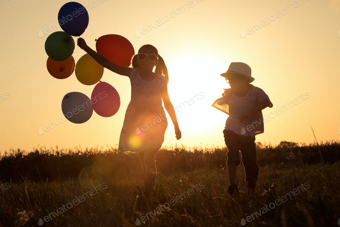 Silhouette of two happy children which playing on the field at t