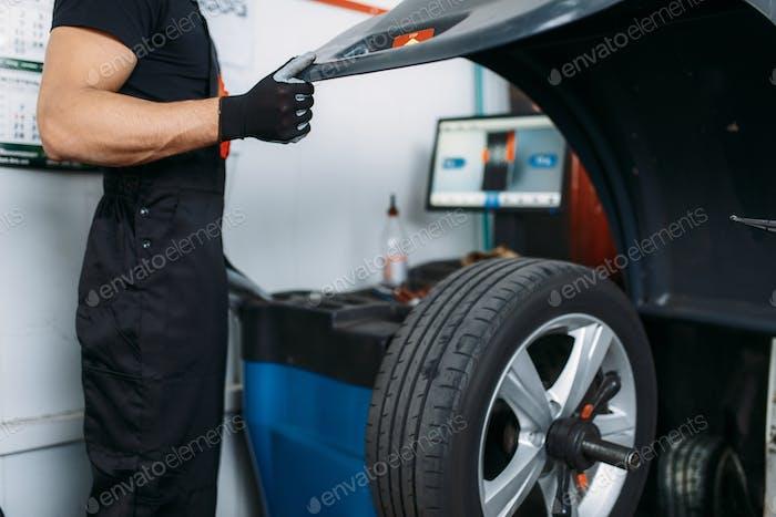 Mechanic fixing wheel on the balancing machine