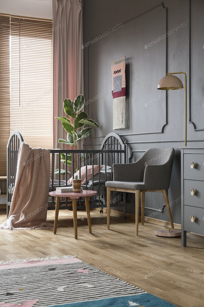 Grey armchair next to bed with pink blanket in kid's bedroom int
