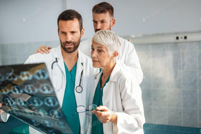 Врачи обсуждают диагноз пациента, глядя на рентген в больнице